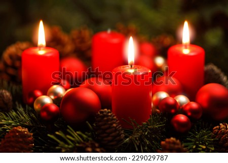 Low-key studio shot of a nice advent wreath with baubles and three burning red candles - stock photo