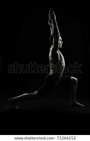 Low key studio shot on black of yoga or stretching - stock photo