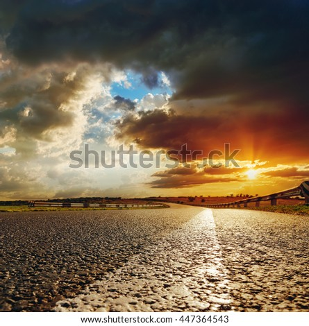 low orange sunset in dramatic clouds over asphalt road - stock photo
