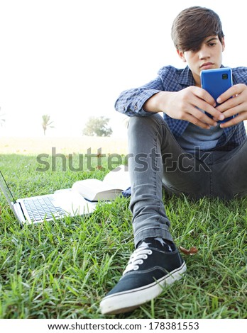Low perspective portrait view of an attractive teenager boy sitting on grass in a park, relaxing using his smartphone while studying for college with his laptop computer. Lifestyle technology. - stock photo