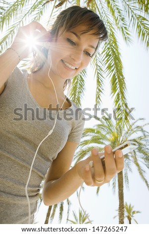 Low portrait view of an attractive young woman having a break from exercising and smiling while listening to music with her mp3 player pad with the sun rays filtering through her hand. - stock photo