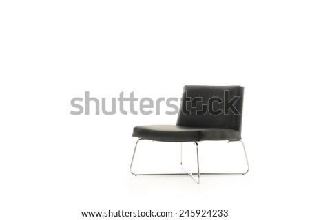 Low profile elegant modern black chair with metal legs isolated on white, three-quarter angled view from the front with copyspace - stock photo