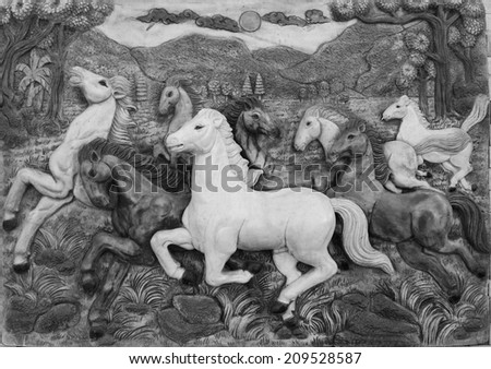 Low relief cement Thai style handcraft of horse on wall. - stock photo