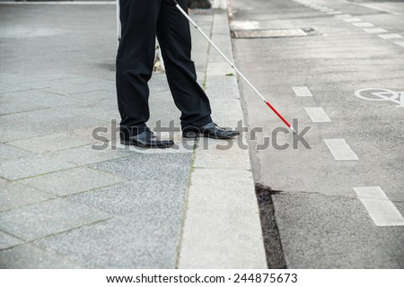 Low Section Of A Blind Person Crossing Street - stock photo