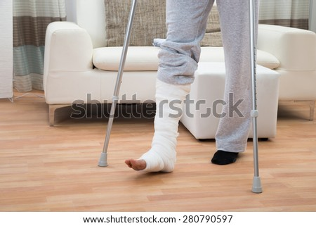 Low Section Of A Disabled Man Using Crutches For Walking - stock photo