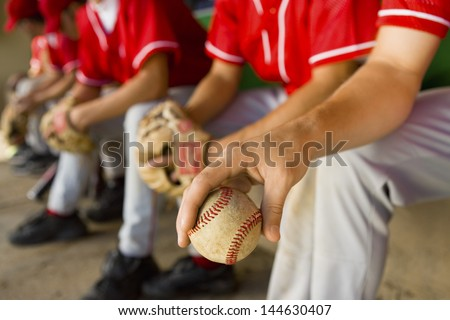 Low section of baseball team mates sitting in dugout with player holding a ball in foreground - stock photo