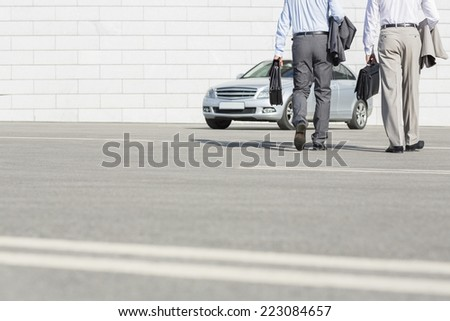 Low section of businessmen carrying briefcases while walking towards car on street - stock photo