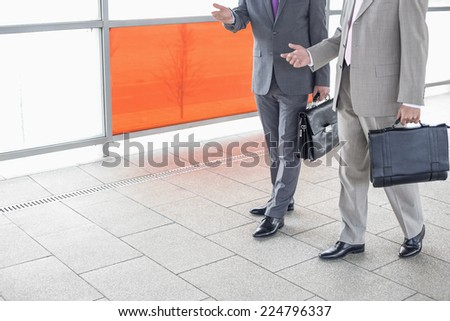 Low section of businessmen communicating while walking in railroad station - stock photo