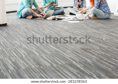 Low section of businesspeople working on floor in creative office - stock photo