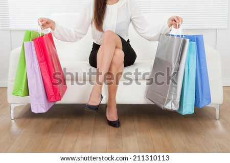 Low section of businesswoman sitting on sofa with multicolored shopping bags on floor at home - stock photo