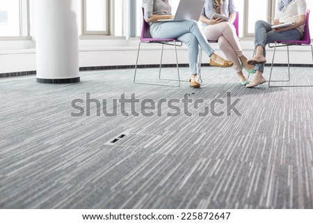 Low section of businesswomen working in creative office - stock photo