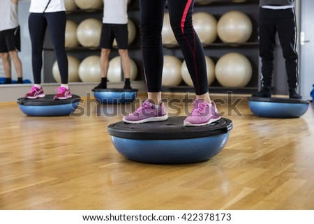Low Section Of Friends Standing On Bosu Ball In Gym - stock photo
