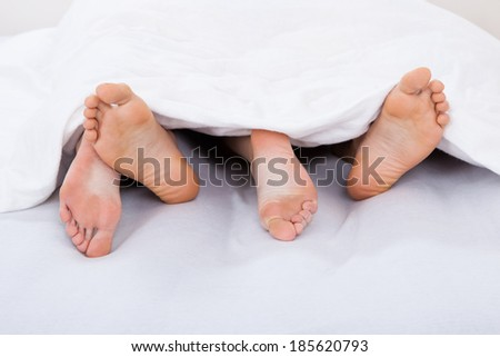 Low section of intimate couple under blanket on mattress at home - stock photo