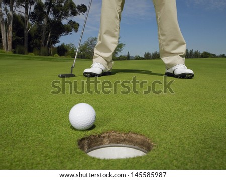 Low section of male golfer on green with ball at hole in foreground - stock photo