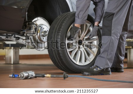 Low section of male mechanic repairing car's tire in repair shop - stock photo
