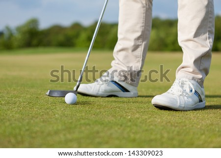 Low section of man hitting golf club with ball on course - stock photo