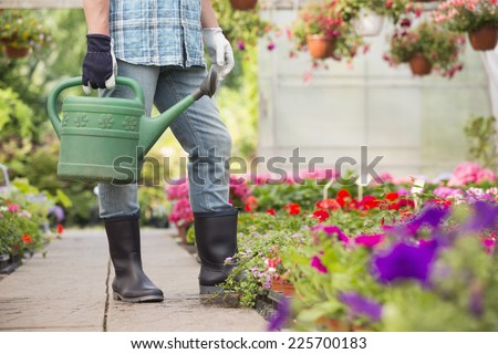 Low section of man holding watering can at greenhouse - stock photo