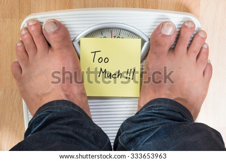 Low section of man standing on weight scale with too much sign - stock photo