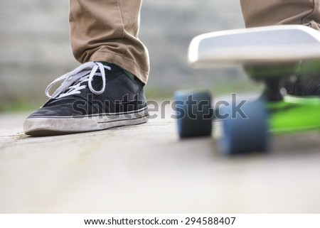 Low section of man with skateboard on footpath - stock photo