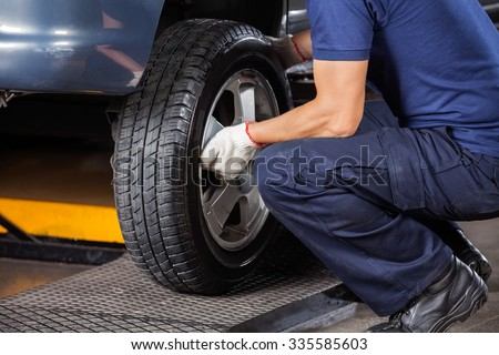 Low section of mechanic fixing car tire at auto repair shop - stock photo