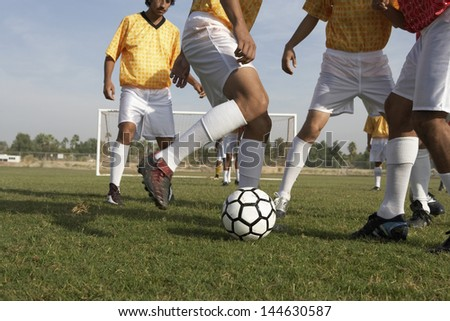 Low section of men playing soccer on the field - stock photo