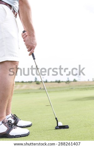 Low section of mid-adult man playing golf against clear sky - stock photo