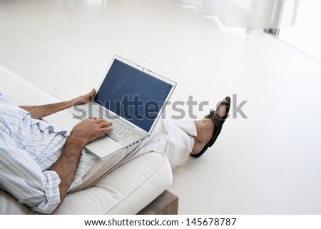 Low section of middle aged man using laptop on sofa in living room - stock photo