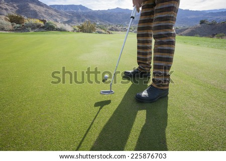 Low section of senior male golfer playing at golf course - stock photo