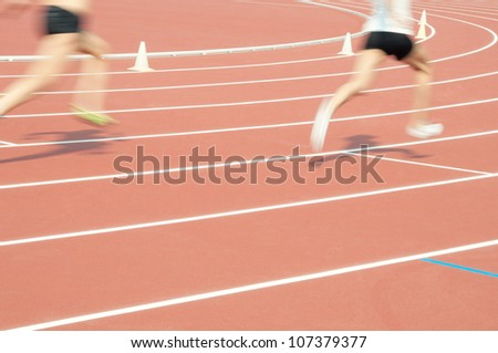 Low section of two athletes sprinting at the stadium, blurred motion, focus on the sports track - stock photo