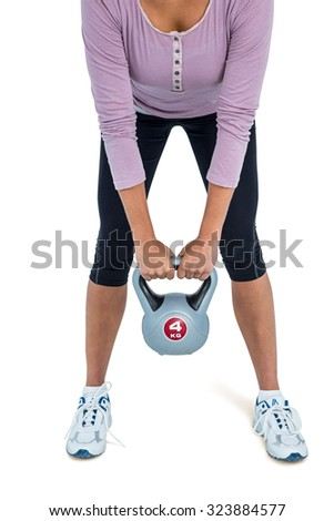 Low section of woman exercising with kettlebell over white background - stock photo