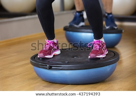 Low Section Of Woman Standing On Bosu Ball - stock photo