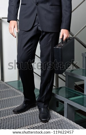 Low section of young businessman carrying briefcase by steps - stock photo
