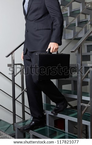 Low section of young businessman descending stairs at office - stock photo