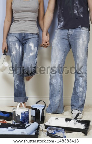 Low section of young couple holding hands with painting tools in foreground - stock photo