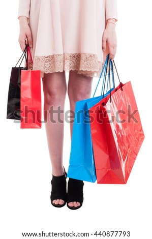 Low section of young stylish girl carrying colorful shopping bags as fashion and consumerism concept isolated on white background - stock photo