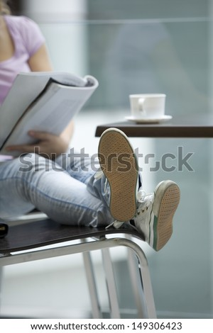 Low section of young woman reading magazine in shopping mall - stock photo