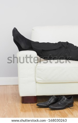 Low section side view of a young businessman resting on sofa in the living room at home - stock photo