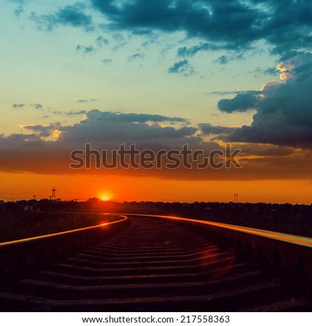 low sun over railroad to horizon in sunset - stock photo