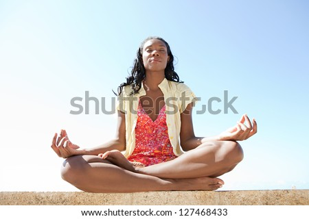 Low view of a healthy and attractive african american woman in a yoga position meditating against a bright blue sky on a sunny day. - stock photo