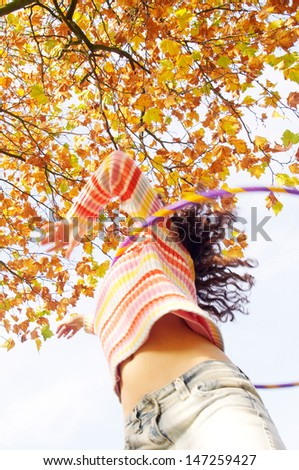 Low view of an active teenager girl playing hoola hoop in a park with orange and brown leaves on the trees, having fun and playing during a sunny autumn day. - stock photo