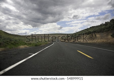 Low view of the road ahead dark clouds above. - stock photo