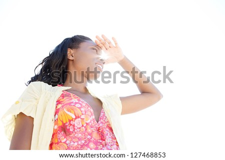 Low view portrait of an attractive black woman on holiday shading her eyes with her hand against a clean sky, with sun rays filtering trough. - stock photo