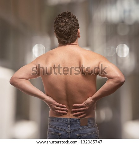 Lower back pain on fit adult man - stock photo