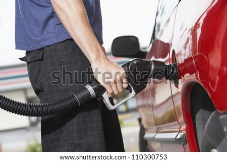 Lower body of a man refueling a car - stock photo