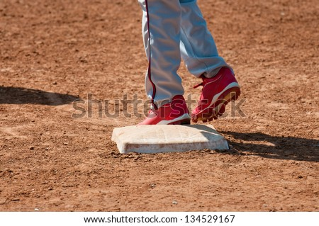 Lower body shot of a teen baseball player standing on base. - stock photo