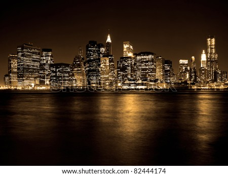 Lower Manhattan in New York City at night with reflection in water - stock photo