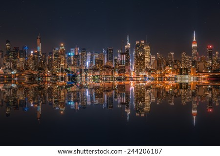 Lower Manhattan skyline at night reflected in water - stock photo