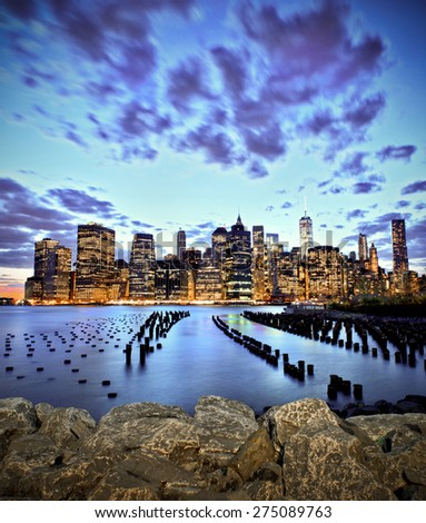 Lower manhattan skyline long exposure seen from Brooklyn Bridge Park in NY at sunset - stock photo