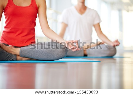 Lower part of slim female and man on background meditating in pose of lotus in gym - stock photo