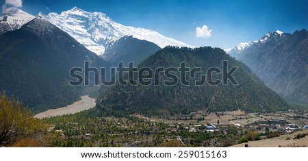 Lower Pisang village and Peak Annapurna II on a Annapurna Circuit - most popular turists trek in Himalayan mountain massive in Nepal. - stock photo